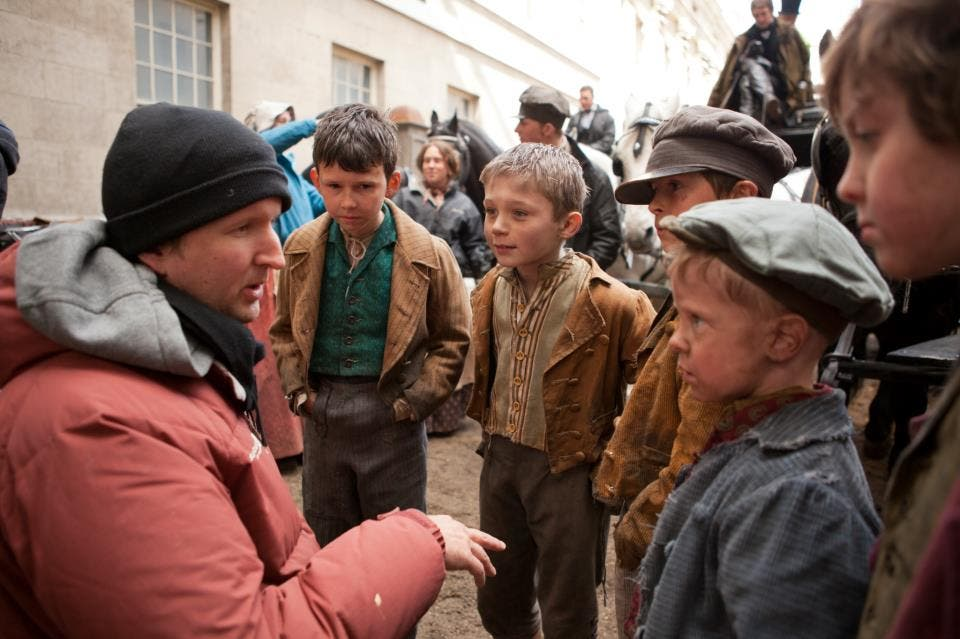 Director Tom Hooper with some of the younger stars on the set of Les Misérables!
