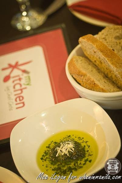 Freshly baked bread with pesto dip, in olive oil topped with cheese