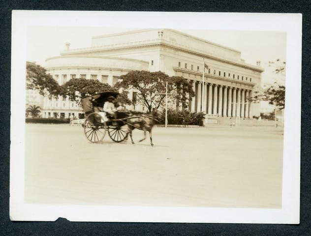 """""""The Manila post office with a """"carramitta' in the foreground. That kind of transportation is restricted to service men due danger of holdups at night."""""""
