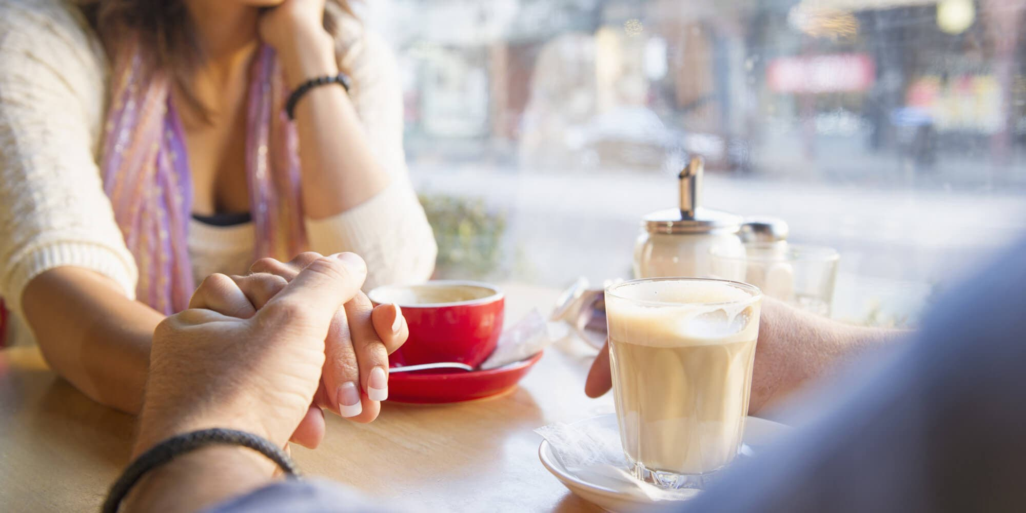 Couple holding hands in cafe