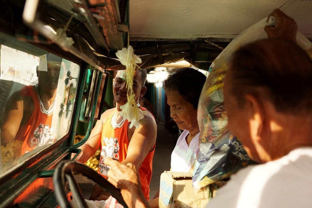 With the caller helping out the passenger get on the jeepney